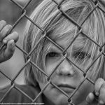 Boy looking through fence